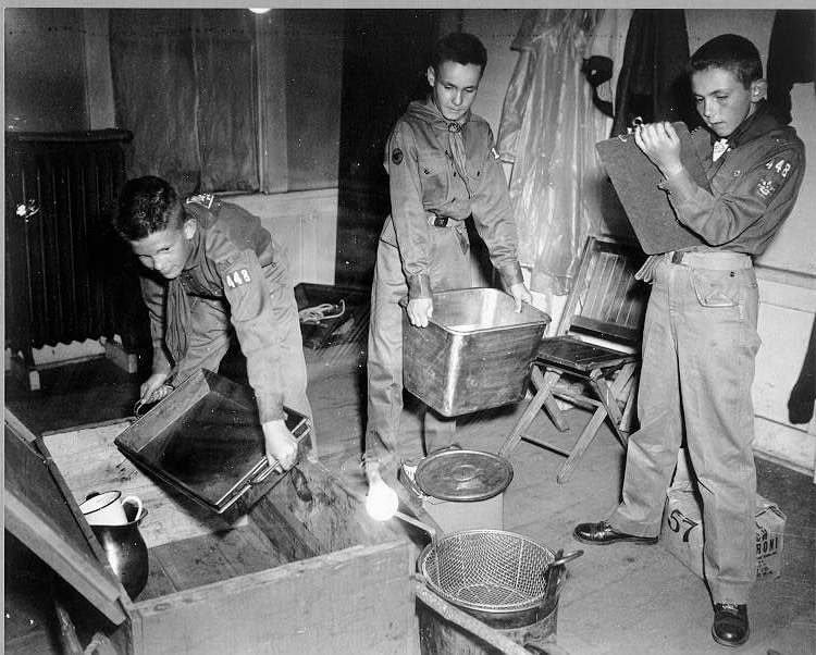In preparation of a camping trip in 1956, these Boy Scouts load gear into a trunk.