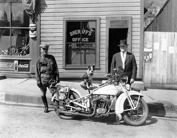 Dodo poses on Sam Billings' (left) motorcycle with Ephraim Adamson (right). Pop Jenks Collection